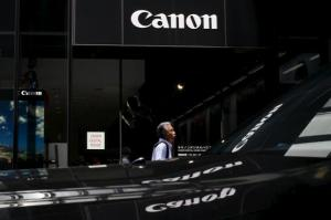 A man walks past a showroom of Japanese imaging and optical products manufacturer Canon in Tokyo