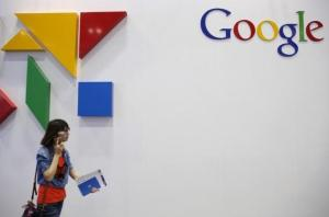 Woman walks past a logo of Google at the Global Mobile Internet Conference (GMIC) 2015 in Beijing