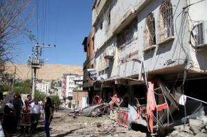 People gather outside of a damaged building after clashes between Turkish security forces and members of YDG-H in Silvan