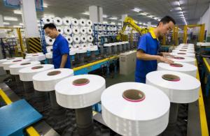 Employees work along a production line of a textile factory in Suzhou