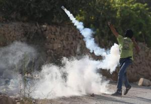 Palestinian protester returns a tear gas canister fired by Israeli troops during clashes following the funeral of Palestinian youth Laith al-Khaldi, in Jalazoun refugee camp near the West Bank city of Ramallah