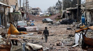 A man walks in a street with abandoned vehicles and damaged buildings in the northern Syrian town of Kobani