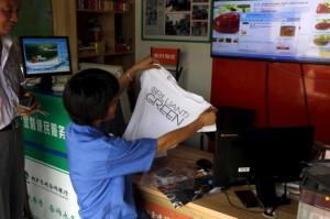 Customer looks at a T-shirt she bought at an Alibaba rural service centre in Jinjia Village, Tonglu, Zhejiang province, China