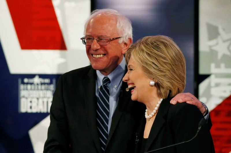 Democratic U.S. presidential candidate Clinton shares a laugh with Sanders at the conclusion of the second official 2016 U.S. Democratic presidential candidates debate in Des Moines