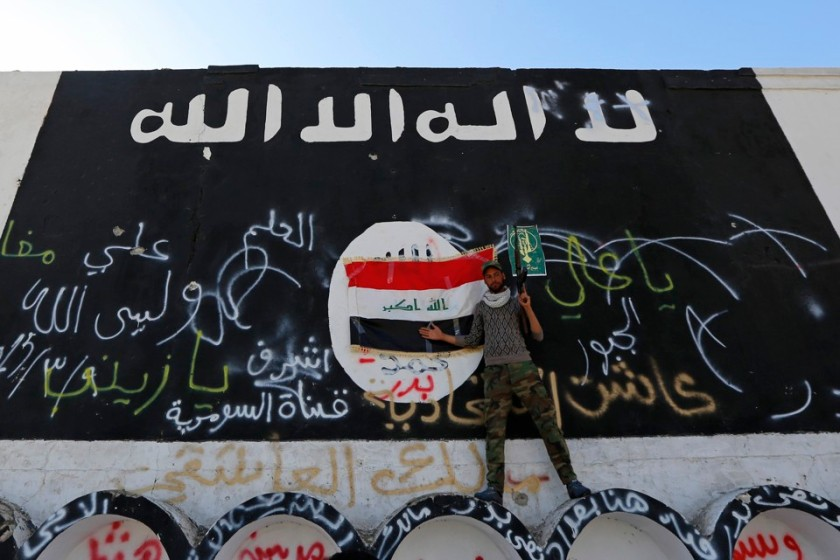 A member of militias known as Hashid Shaabi stands next to a wall painted with the black flag commonly used by Islamic State militants, in the town of al-Alam